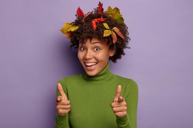 Horizontaal schot van glimlachende dame met gelukkige uitdrukking, wijst vingerpistoolgebaar in camera, draagt groene poloneck Gratis Foto