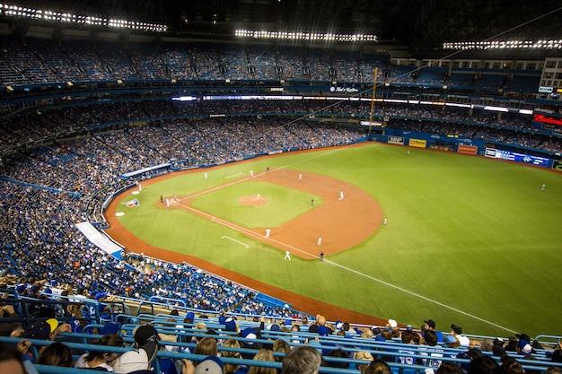 Horizontaal schot van het drukke honkbalstadion van yankee en spelers in het veld Gratis Foto