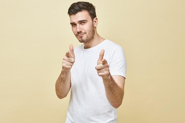 Horizontaal schot van knappe charismatische jonge man met zwart haar en stoppels poseren geïsoleerd wijzende vingers, met zelfverzekerde flirterige gezichtsuitdrukking, jou kiezen. lichaamstaal Gratis Foto