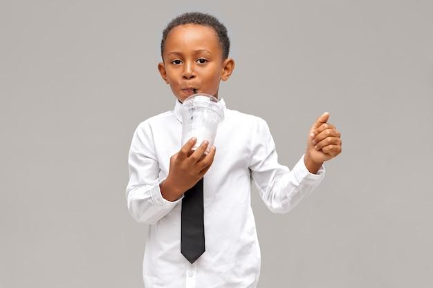 Horizontaal schot van leuke donkere jongen die een wit overhemd en een zwarte das draagt en van vers sap geniet. knappe afro-amerikaanse leerling smoothie of milkshake drinken uit plastic glas met stro Gratis Foto
