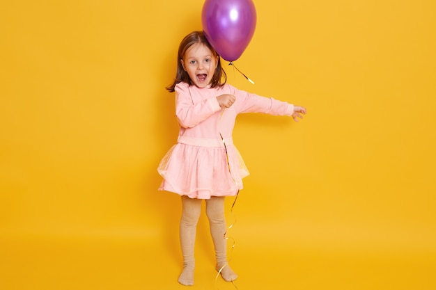 Horizontaal schot van meisje met purpere ballon dat over geel wordt geïsoleerd al vrouwelijk kind dat somethig schreeuwt, herbirtday viert, jong geitje dat rooskleurige kleding draagt en donker haar heeft. Gratis Foto