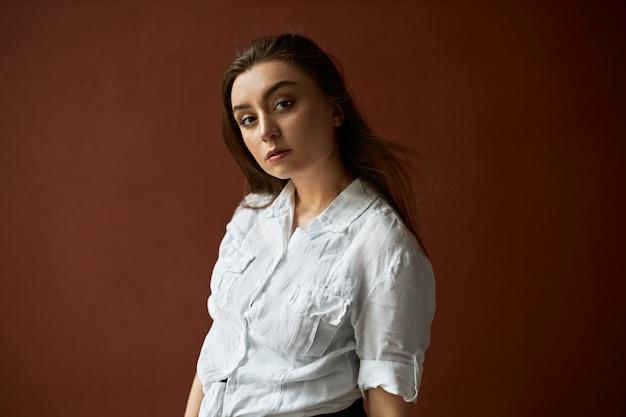 Horizontaal schot van modieuze jonge vrouw met losse bruin haar camera kijken met doordachte peinzende gezichtsuitdrukking, gekleed in wit overhemd. zelfverzekerd stijlvol meisje poseren in studio Gratis Foto