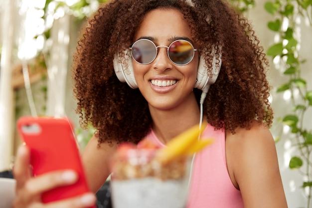Horizontaal schot van mooi jong vrouwelijk model met donkere huid en krullend haar, draagt sunglaases, verbonden met hoofdtelefoons en slimme telefoon, luistert audiotrack. mensen en entertainment concept Gratis Foto