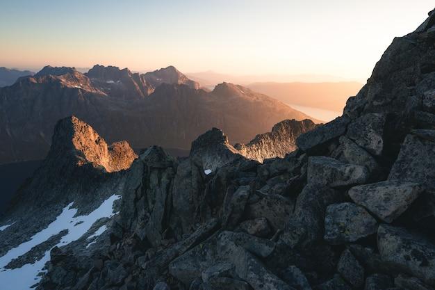 Horizontaal schot van rotsachtige bergen die in sneeuw tijdens zonsopgang worden behandeld Gratis Foto