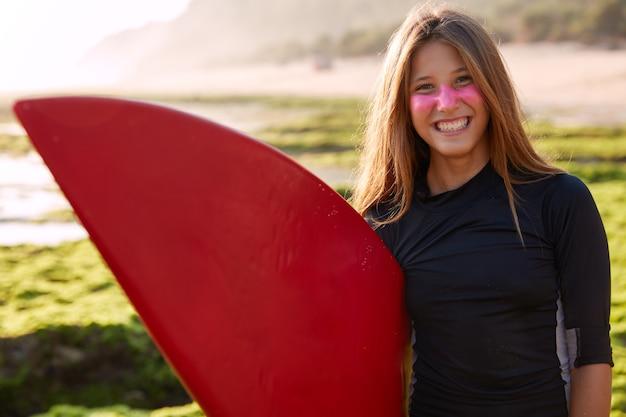 Horizontaal schot van vrij glimlachende kaukasische jonge vrouw met lang steil haar Gratis Foto