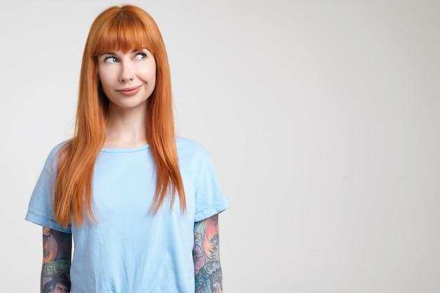 Horizontale foto van jonge langharige roodharige vrouw met tatoeages die haar gezicht grimassen terwijl ze verwonderd opzij kijkt, geïsoleerd tegen een witte achtergrond Gratis Foto