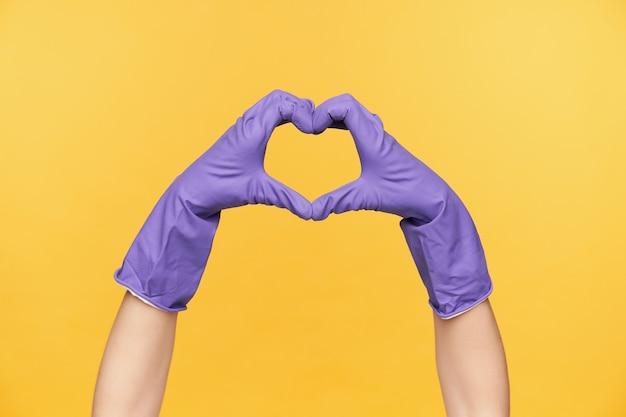 Horizontale foto van opgeheven handen gekleed in rubberen handschoenen met liefde teken, hart vormen met vingers terwijl wordt geïsoleerd op gele achtergrond Gratis Foto