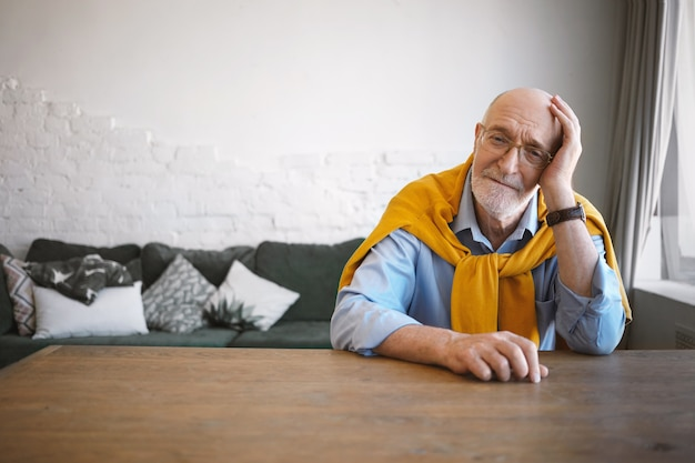 Horizontale foto van stijlvolle volwassen zestigjarige advocaat zittend op zijn werkplek in modern kantoor interieur, met een kleine pauze, hoofd bij de hand rustend, trui om zijn nek dragen, moe kijken Gratis Foto