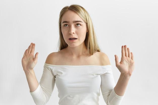 Horizontale geïrriteerde geïrriteerde jonge blonde vrouw in stijlvolle top rollende ogen en stop gebaar maken Gratis Foto