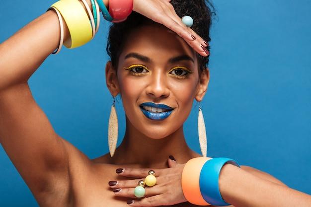 Horizontale mooie mulatvrouw met kleurrijke make-up en krullend haar in broodje die toebehoren op haar wapens tonen geïsoleerd, over blauwe muur Gratis Foto