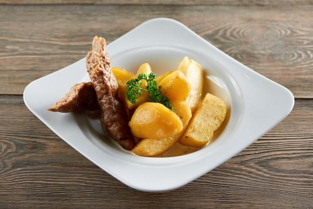 Horizontale opname van een plaat met gebakken aardappelschijfjes en kippenworst op een houten tafel diner maaltijd lunch avondmaal vlees eten hongerig heerlijke groente gegrild geroosterd. Gratis Foto
