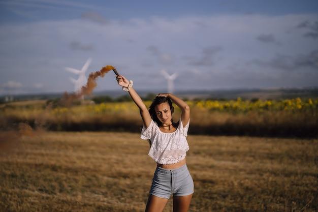 Horizontale opname van een vrouw poseren met een rookbom op een achtergrond van velden en windmolens Gratis Foto