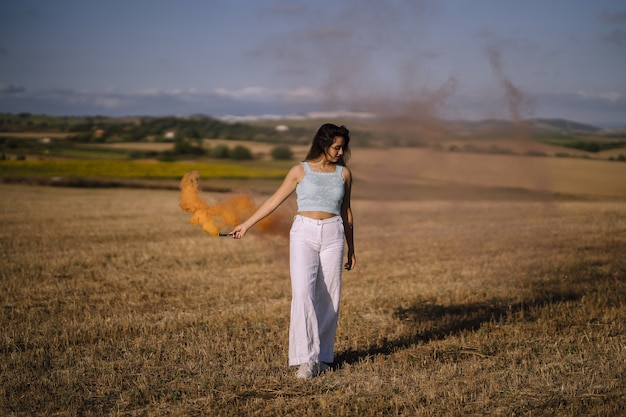 Horizontale opname van een vrouw poseren met een rookbom op het veld Gratis Foto