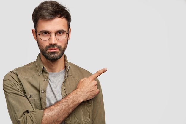 Horizontale opname van knappe ongeschoren jonge man met donkere stoppels, strikte blik, heeft ernstige uitdrukking, gekleed in modieus shirt, wijst rechts opzij Gratis Foto