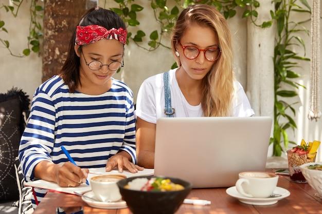 Horizontale opname van serieuze dames kijken samen naar webinar, verbonden met wifi in cafetaria Gratis Foto