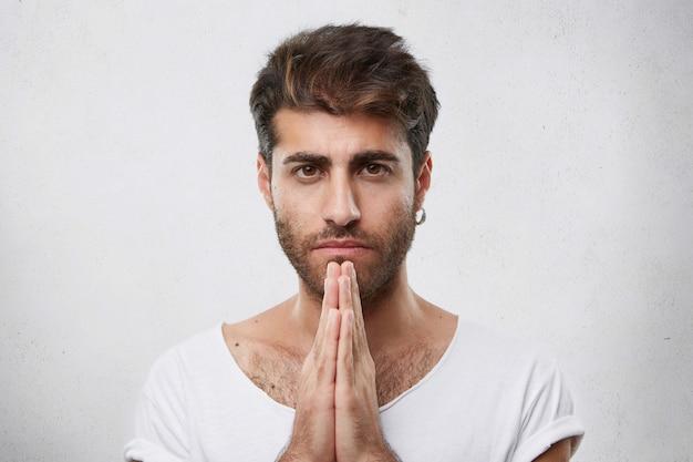 Horizontale portret van knappe man met trendy kapsel en baard dragen oorbel en wit t-shirt houden zijn handen samen bidden met ogen vol geloven om beter te vragen om iets Gratis Foto