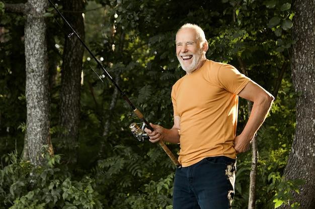 Horizontale portret van knappe vrolijke bejaarde blanke mannelijke gepensioneerde m / v in vrijetijdskleding lachen gelukkig terwijl buiten staan met hengel, vissen vangen op rivieroever in de ochtend Gratis Foto