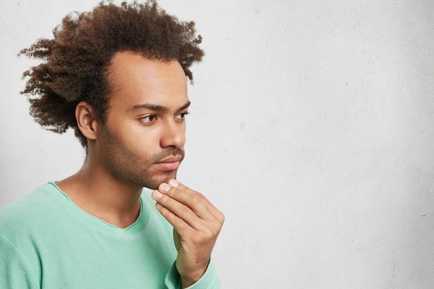 Horizontale portret van peinzende gemengd ras man met afro kapsel, houdt de hand op de kin Gratis Foto