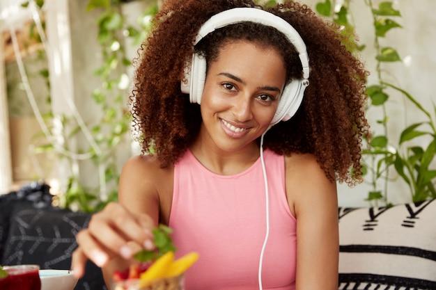 Horizontale schot van positieve vrouw luistert naar nieuwe muziek in moderne koptelefoon terwijl op vriend in café wacht, fruit dessert eet, geniet van een goede nachtrust. afro-amerikaanse student recreëren na lezingen Gratis Foto