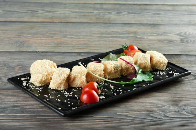 Horizontale shot van kaas ballen met sezam geserveerd op een bord met kerstomaatjes en sommige groenen smakelijke heerlijke hapjes restaurant gastronomisch menu delicatesse eten concept. Gratis Foto