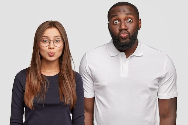 Horizontale weergave van aangenaam uitziende interraciale man en vrouw houdt de lippen rond Gratis Foto