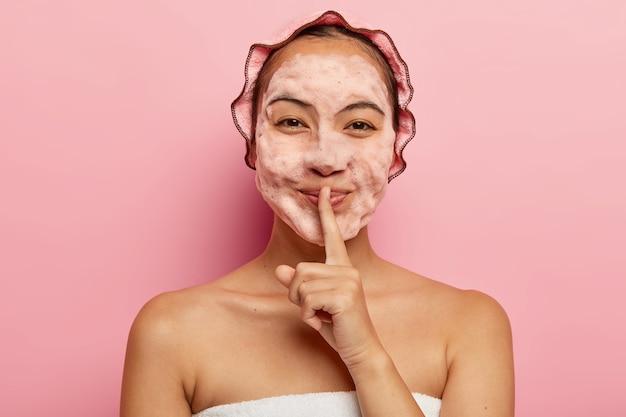 Horizontale weergave van mooie aziatische dame met schuim op gezicht, reinigt van vuil, wil een frisse blik hebben, maakt stilte gebaar, draagt een douchemuts, ziet er gelukkig uit. netheid en hygiëne concept Gratis Foto