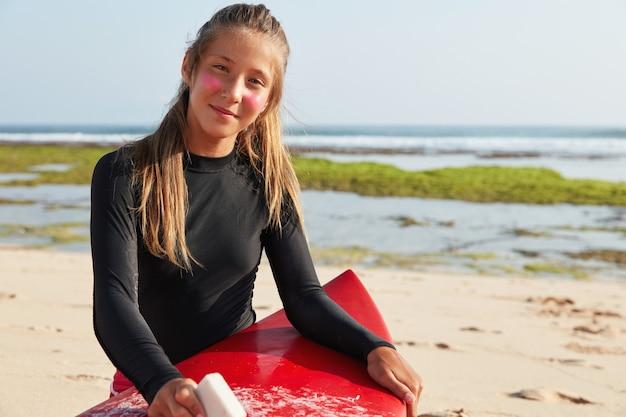 Horizontale weergave van professionele surfer maakt zich klaar voor surfen, waxen bord met wax, wil dubbele spinner demonstreren Gratis Foto