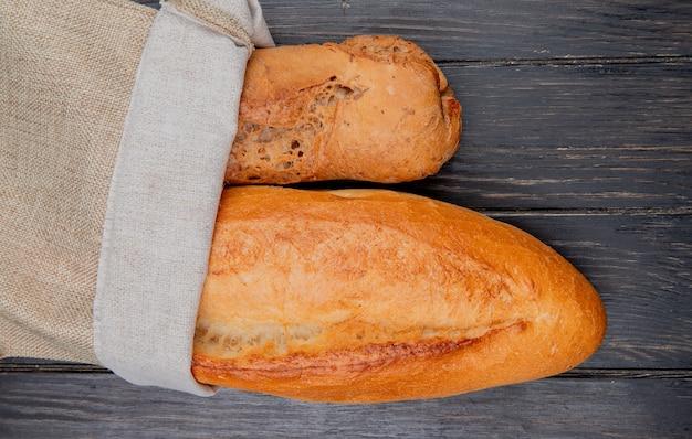Horizontale weergave van stokbrood als zwart en vietnamees in zak op houten oppervlak Gratis Foto