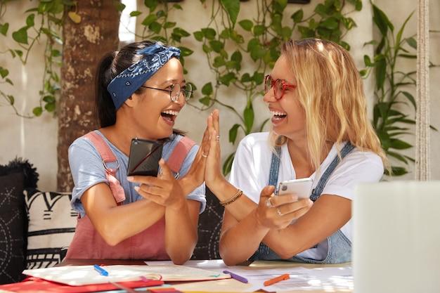 Horizontale weergave van succesvolle vrouwelijke partners van gemengd ras geven vijf aan elkaar, zijn het eens met een goed idee voor het maken van een project Gratis Foto