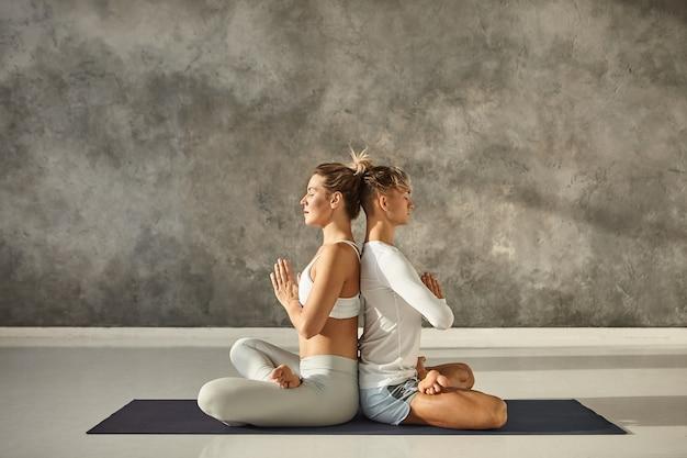 Horizontale zijaanzicht van aantrekkelijke jonge paar yoga samen binnenshuis beoefenen. vreedzame blanke man en vrouw zitten rug aan rug in lotus houding, hand in hand in namaste, ogen gesloten Gratis Foto