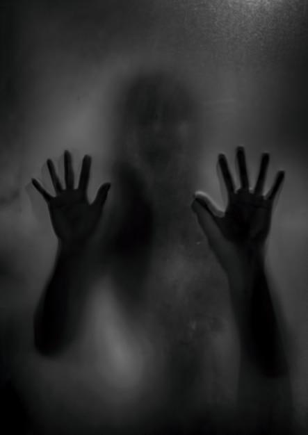 Horrorspook meisje achter het matte glas in zwart en wit. halloween-festivalconcept. Premium Foto