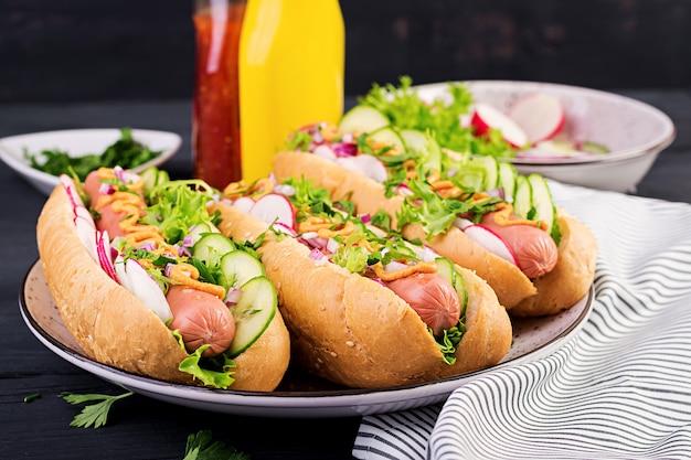 Hotdog met worst, komkommer, radijs en sla Premium Foto