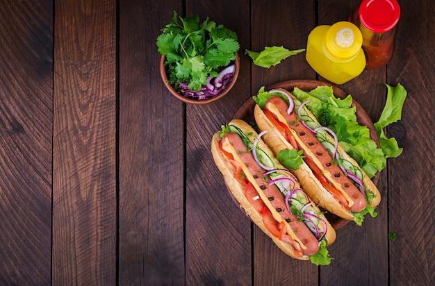 Hotdog met worst, komkommer, tomaat en sla op donkere houten lijst. zomer hotdog. bovenaanzicht Gratis Foto