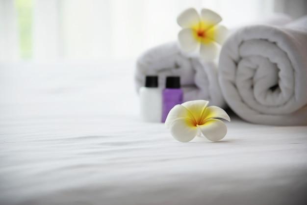 Hotelhanddoek en shampoo en zeepbadfles die op wit bed met verfraaide plumeriabloem wordt geplaatst - ontspan vakantie bij het concept van de hoteltoevlucht Gratis Foto