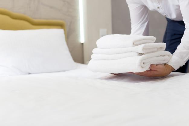 Hotelpersoneel dat kussen op bed opzet Premium Foto