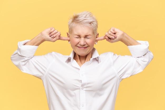 Hou je mond! geïsoleerd beeld van gefrustreerde boze volwassen vrouw met geverfd pixiehaar die de ogen gesloten houdt en de oren verstopt, kan geen harde geluiden of lawaai uitstaan, gestrest zijn tijdens ruzie of ruzie Gratis Foto