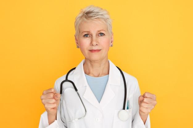 Hou je sterk. portret van ernstige senior vrouwelijke arts in medisch uniform balde vuisten, patiënten aanmoedigen om tegen ziekte te vechten, haar blik vol hoop en vastberadenheid. Gratis Foto
