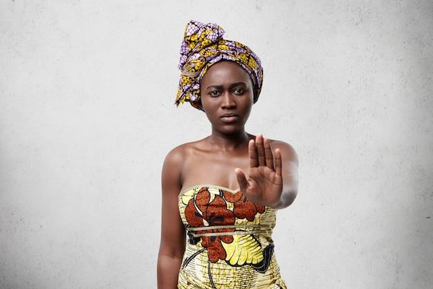 Hou op! afrikaanse vrouw met donkere gladde huid die traditionele kleding draagt die haar handpalm toont en ontkent iets niet te doen. zelfverzekerd donkerhuidig vrouwtje zonder gebaar. veto en vraagconcept Gratis Foto