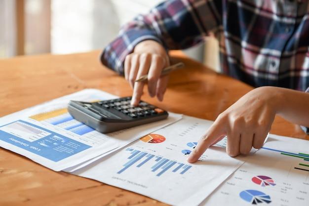 Houd de aanwijzer bij de grafiek en de andere hand vast en druk op de rekenmachine. Premium Foto