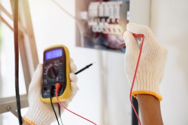 Houd de digitale multimeter vast om de elektrische stroom op de stroomonderbreker te controleren. focus op een gehandschoende hand. Premium Foto