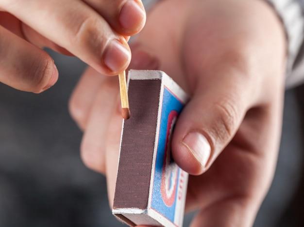 Houd een luciferdoosje vast terwijl je een lucifer slaat. Premium Foto