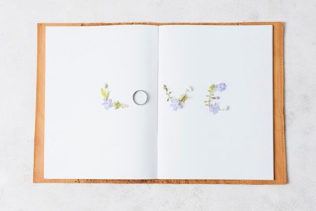 Houd van bloementekst op een open boek over witte achtergrond Gratis Foto