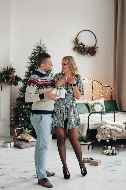 Houdend van echtgenoot die zijn huidige vrouwkerstmis geeft. mooie vrouw verrast door geschenk van echtgenoot te krijgen. Gratis Foto