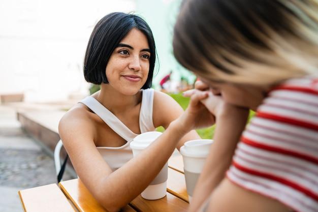 Houdend van lesbisch paar die een datum hebben bij koffiewinkel. Premium Foto
