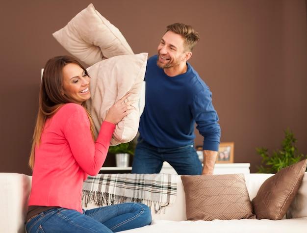 Houdend van paar dat thuis een kussengevecht heeft Gratis Foto