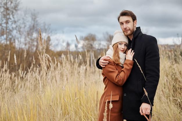 Houdend van paar die op gebied, de herfstlandschap omhelzen Premium Foto