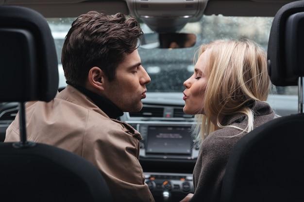 Houdende van paarzitting in auto het kussen met gesloten ogen. Gratis Foto