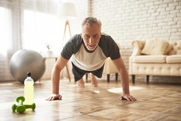 Houding oefening senior man doet plank training. Premium Foto