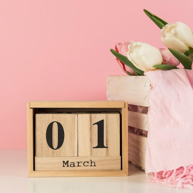 Houten 1st maart-kalender dichtbij de krat met sjaal en tulpen tegen roze achtergrond Gratis Foto