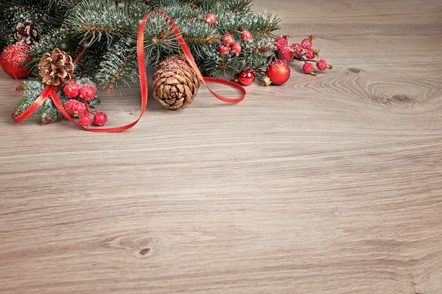 Houten achtergrond met versierde kerstboomtakjes Premium Foto